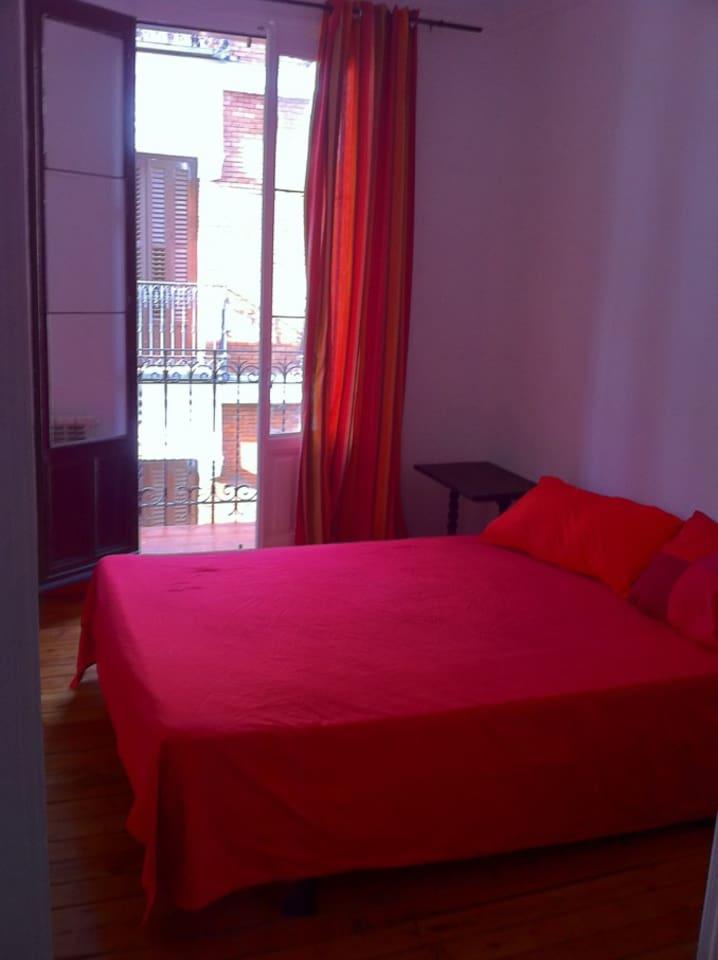 Dormitorio con balcon y cama de matrimonio