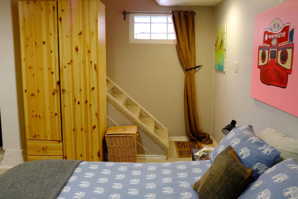 bed looking at the entrance with an empty armoire for your use (also has extra sheets and towels inside for futon and other guests)