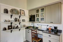 The simple kitchenette includes a desk , a mini fridge, a microwave and coffee station.