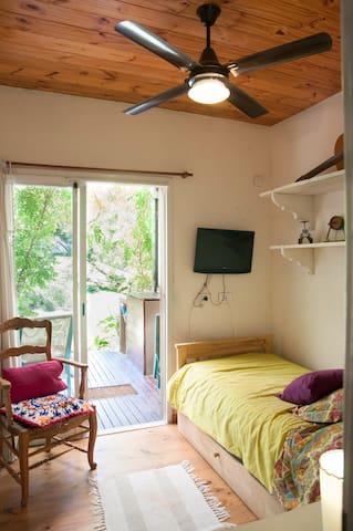 Habitacion con cama de una plaza y otra debajo con carrito. Led y ventilador de techo.