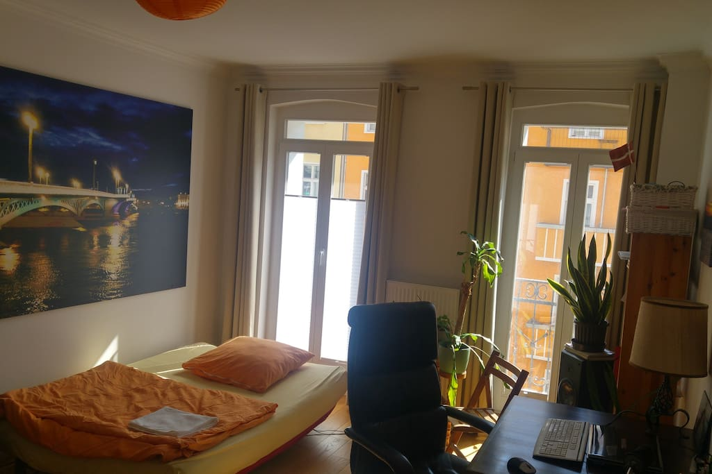 Guestroom including work desk and access to balcony
