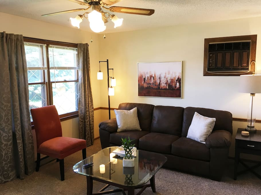 Spacious living room with ceiling fan, lots of lighting, and more!