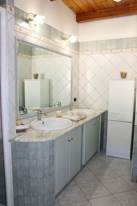 Ampio bagno con doccia e due lavandini, davvero comodo per chi desidera ottimizzare i tempi!