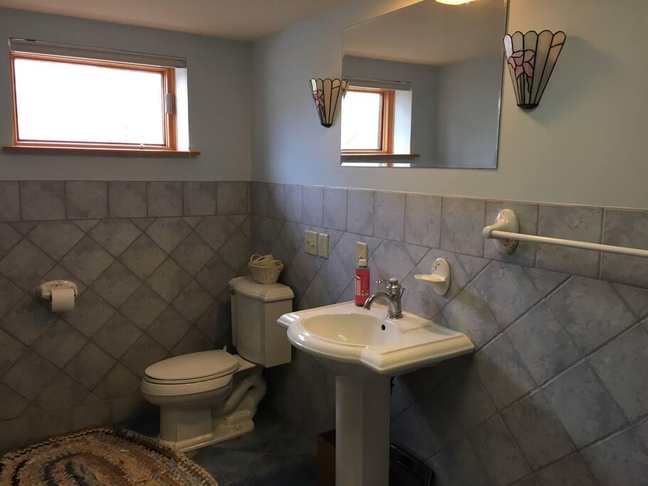 Ground floor bathroom has beautiful tile work and a deep bathtub