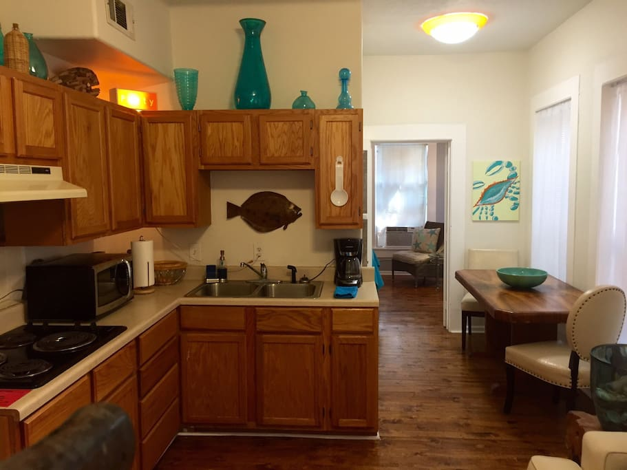 Small kitchen with cooktop and microwave. Dining area.