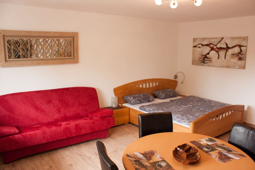 Bequemes 1,80m breites Bett mit hochwertiger Matratze, daneben ein Schlafsofa zum ausziehen für den 3. Gast