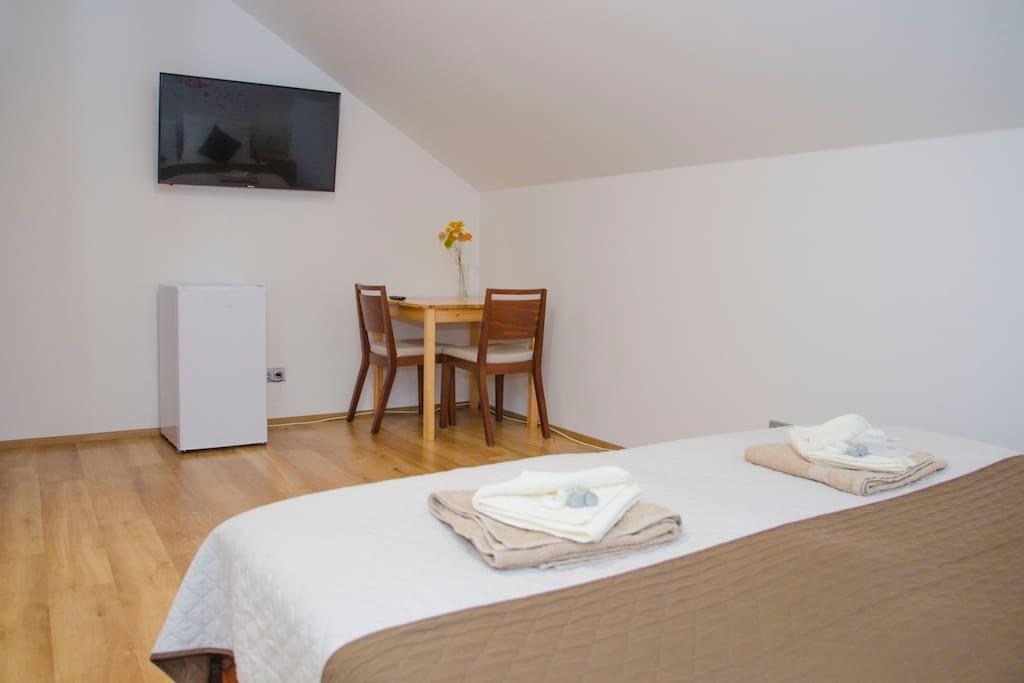 V pokoji je satelitní 4K UHD televize, vlastní lednička, stůl a dvě pohodlné židle. / SAT 4K UHD TV, dedicated fridge, table with two cozy chairs