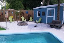 Outside view of backyard, pool and firepit during the day.