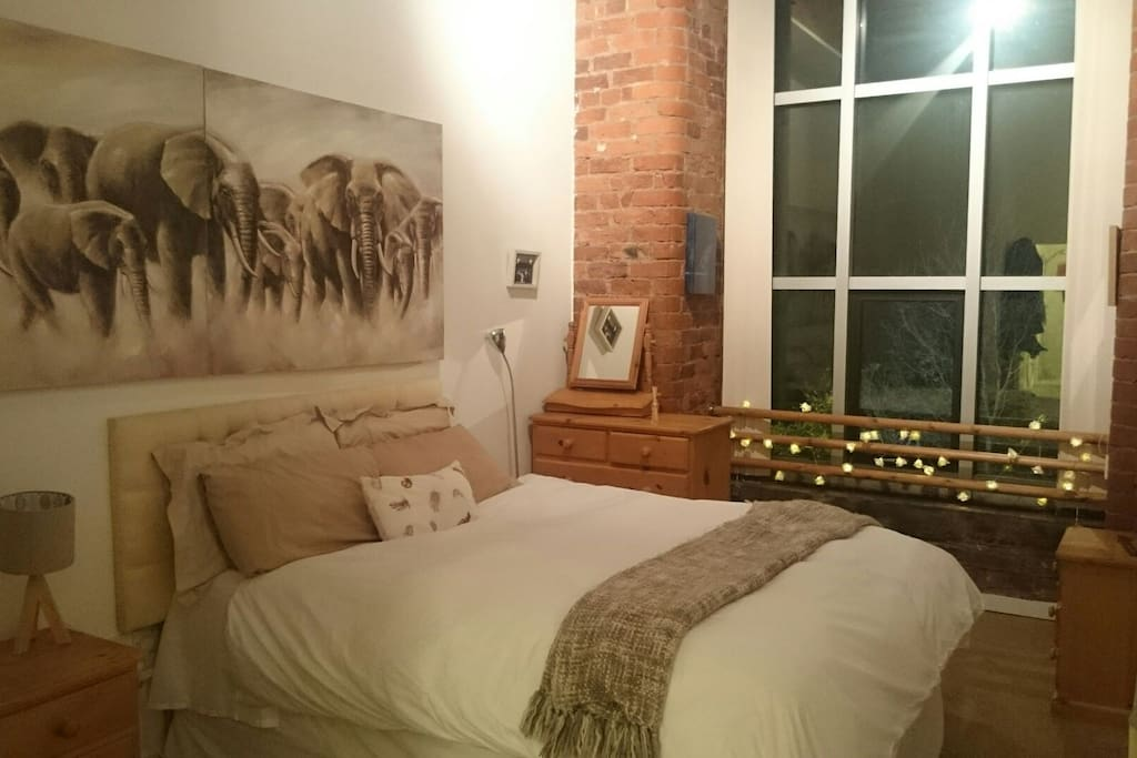 King size bed with high ceilings and exposed brick