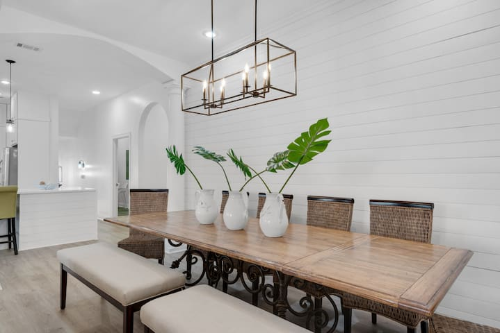 Shiplap walls with farmhouse lighting and a mix of natural woods create a magazine-quality beach chic design.
