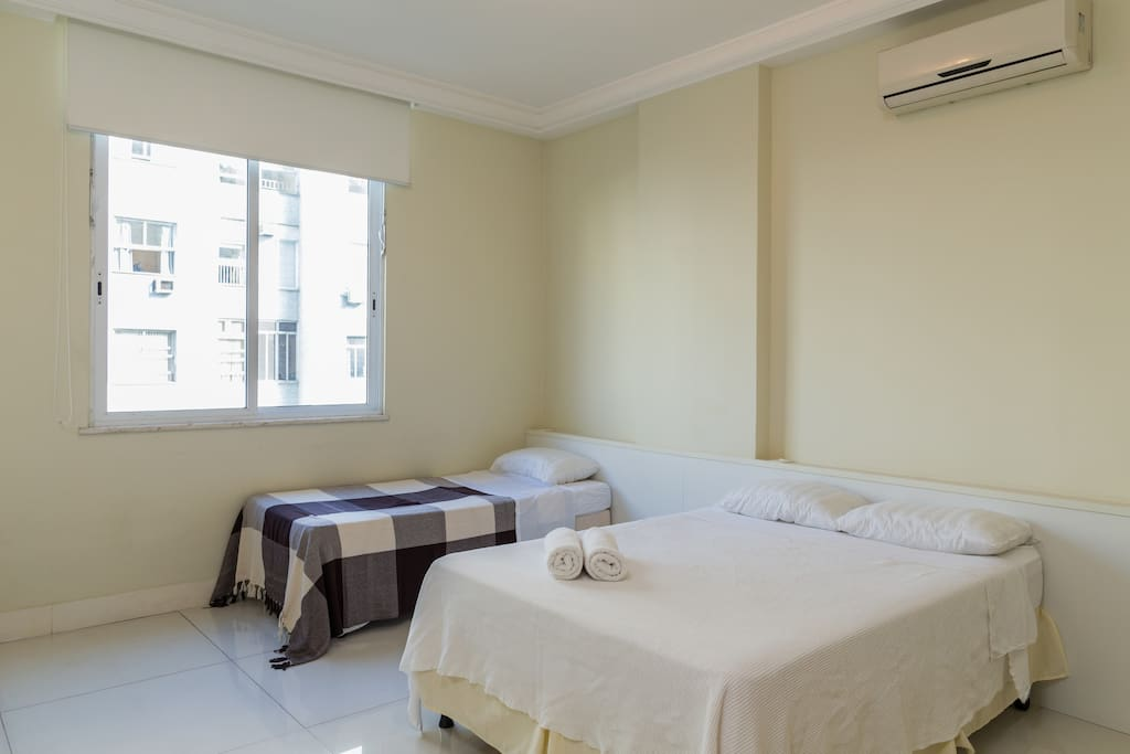 Large Bedroom area with a double bed + 1 single bed and a slider mattress under single bed. Split air con unit and blackout curtain.