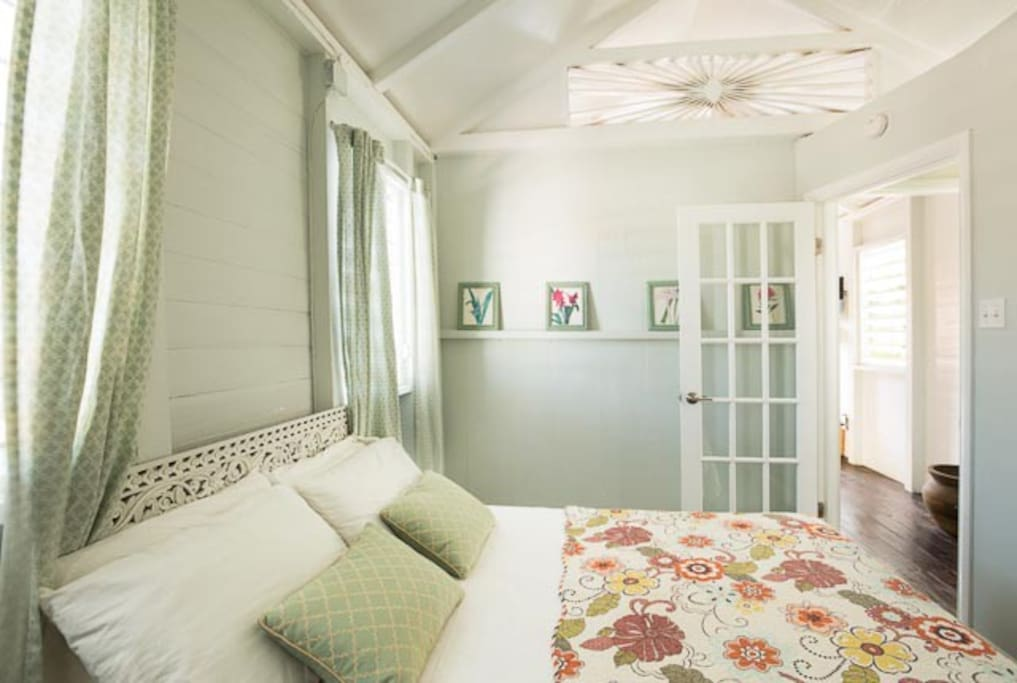 Bedroom, light, airy, with handcrafted historic details, ceiling fan and French door.