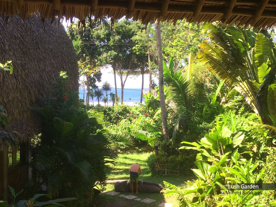 View of lush garden from Family Surf Bungalow's balcony