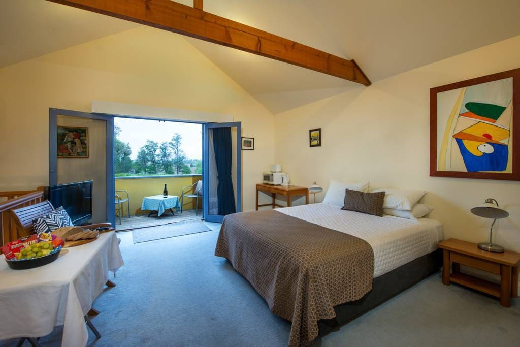 A spacious queen bedroom with a balcony overlooking the vines