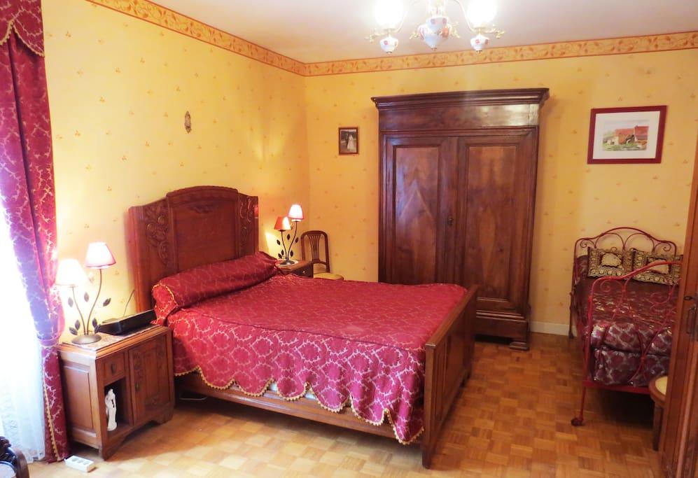 La chambre rouge avec 1 lit double et 1 simple