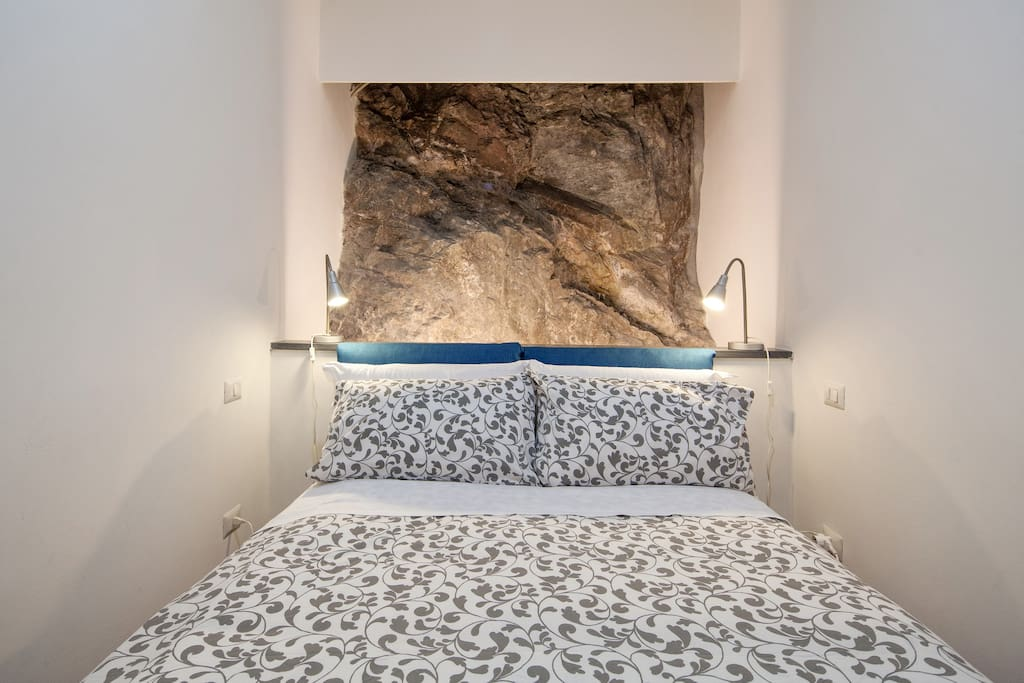 Angolo notte, letto matrimoniale con parete in pietra vera a vista