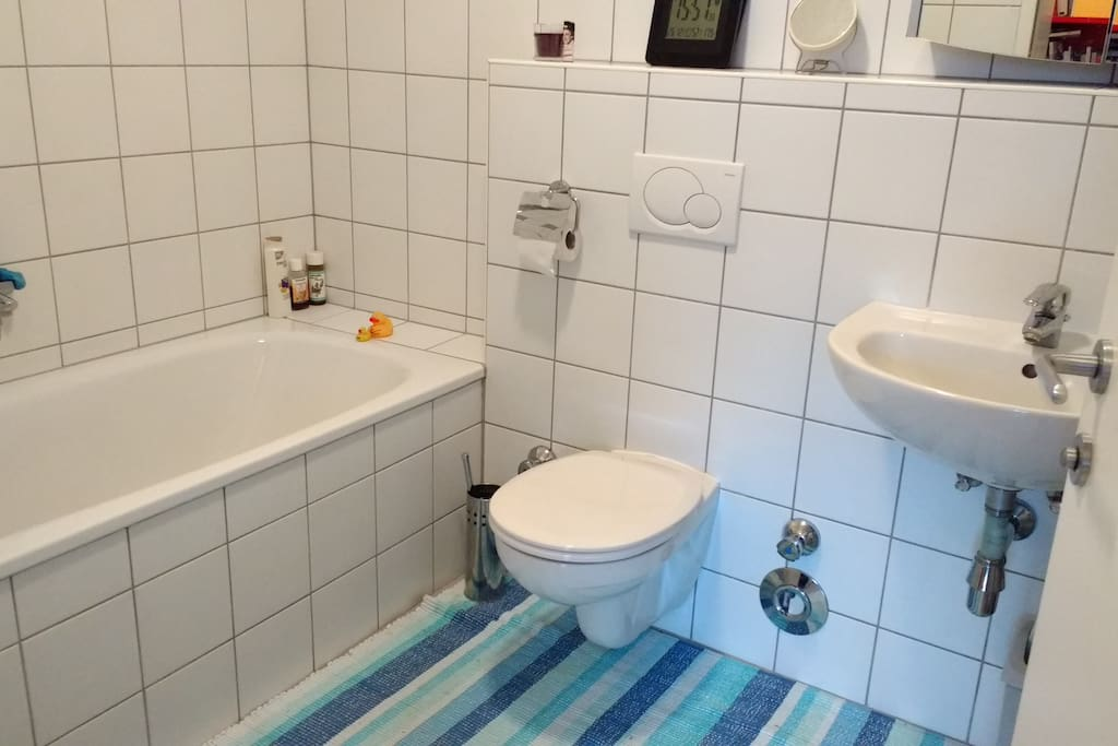 The white bath with tub (or shower curtain). Plus washing maschine and hairdryer.