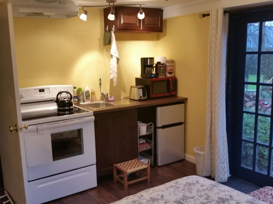 Kitchenette complete with full size stove, mini fridge, microwave, and coffeemaker