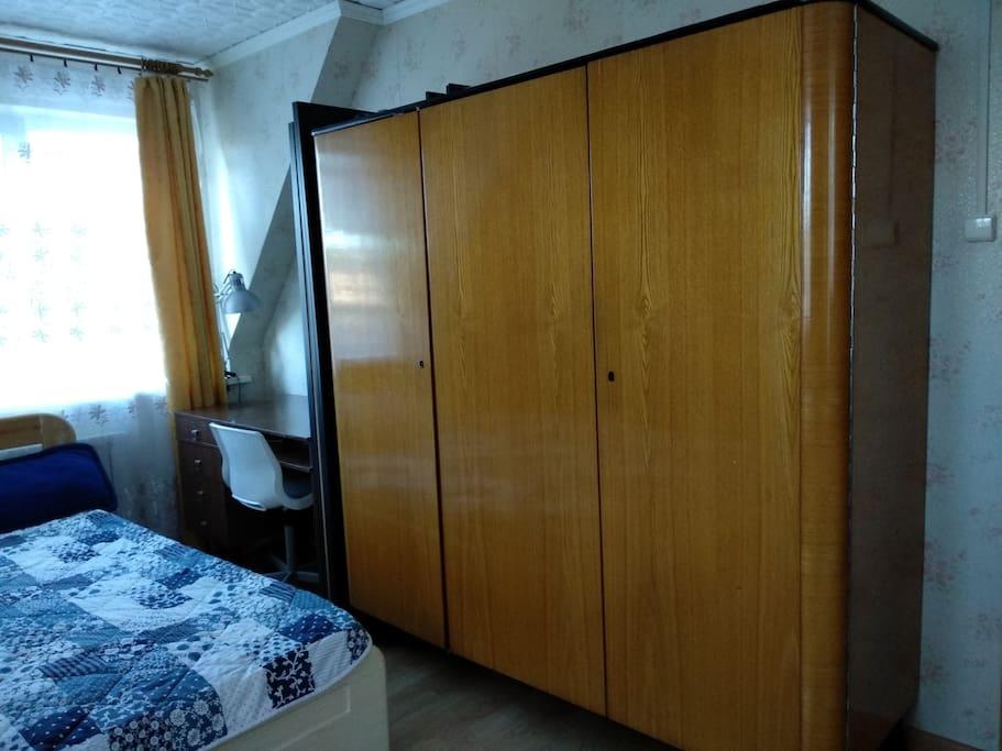 Большой шкаф с зеркалом внутри,  письменный стол, настольная лампа.