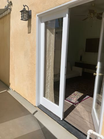 This is the entrance to the suite, private and well lit. French doors with double locks. Enter into a living space with a sleeper couch small fridge and microwave,TV, desk and cabinets.
