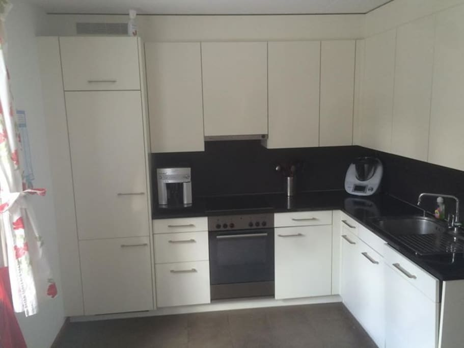 modern fully equipped kitchen including coffee machine and dishwasher.
