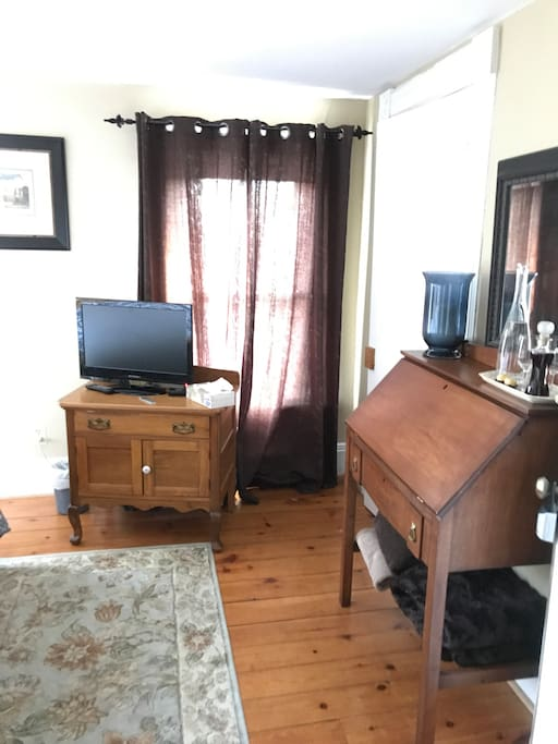 Entrance of bedroom with television and desk.