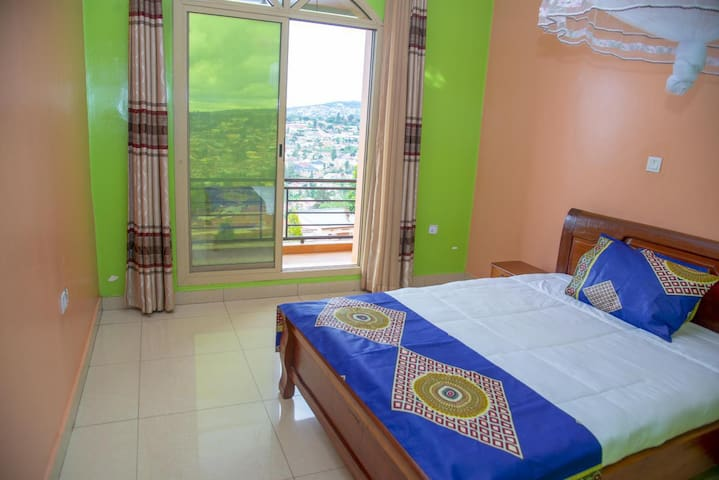 The room is airy with plainty windows to a scenic view of Kigali city.