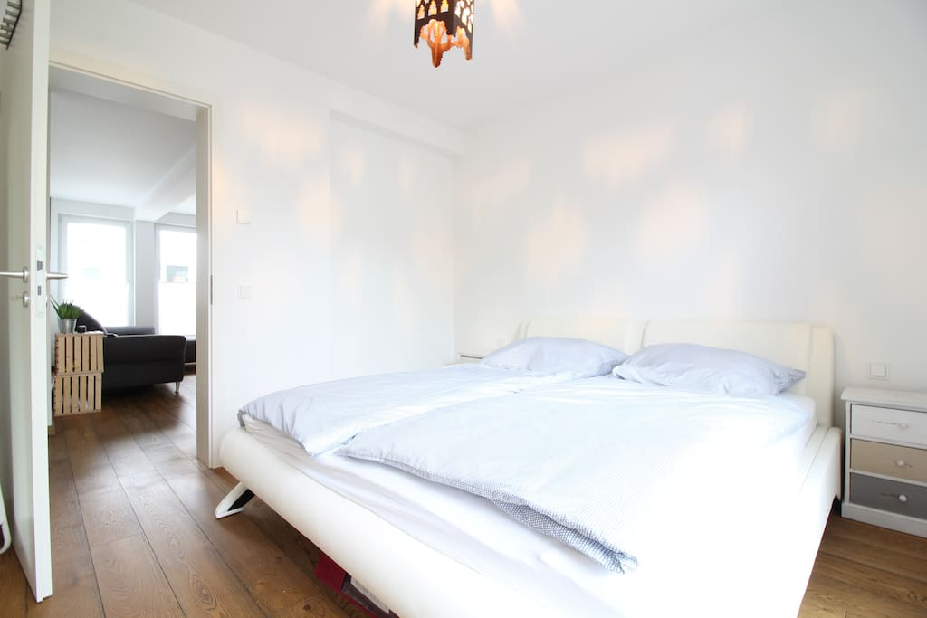 The bright living room is equipped with a huge double bed.