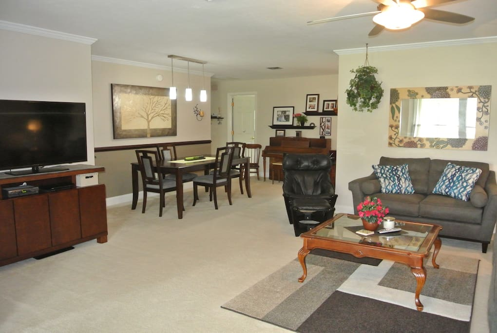 Living room attaches to dining area featuring brand new lighting, a table that can seat up to six, & an upright piano