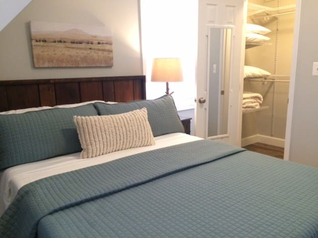 Walk-in closet with extra pillows and blankets.