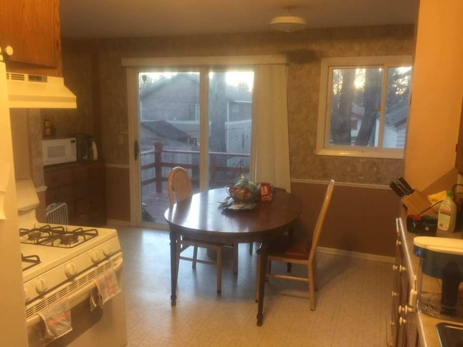Spacious kitchen and dining area, attached to backyard porch.