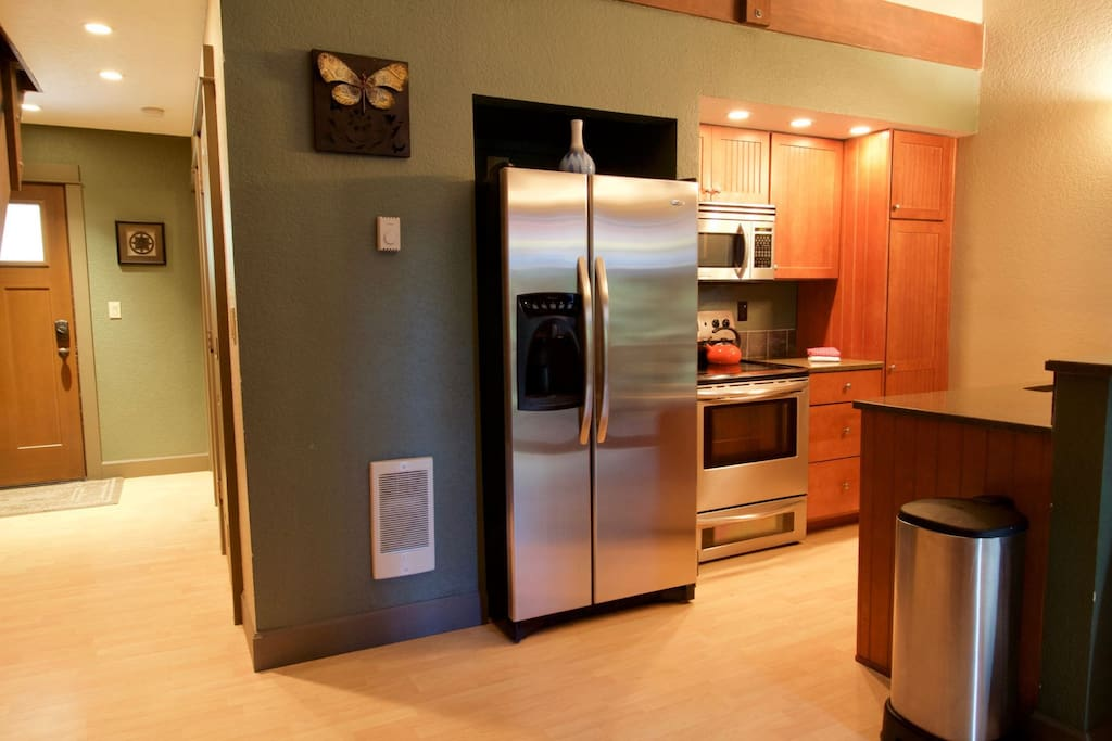 Fully equipped kitchen has a large stainless steel refrigerator, stovetop, microwave and dishwasher