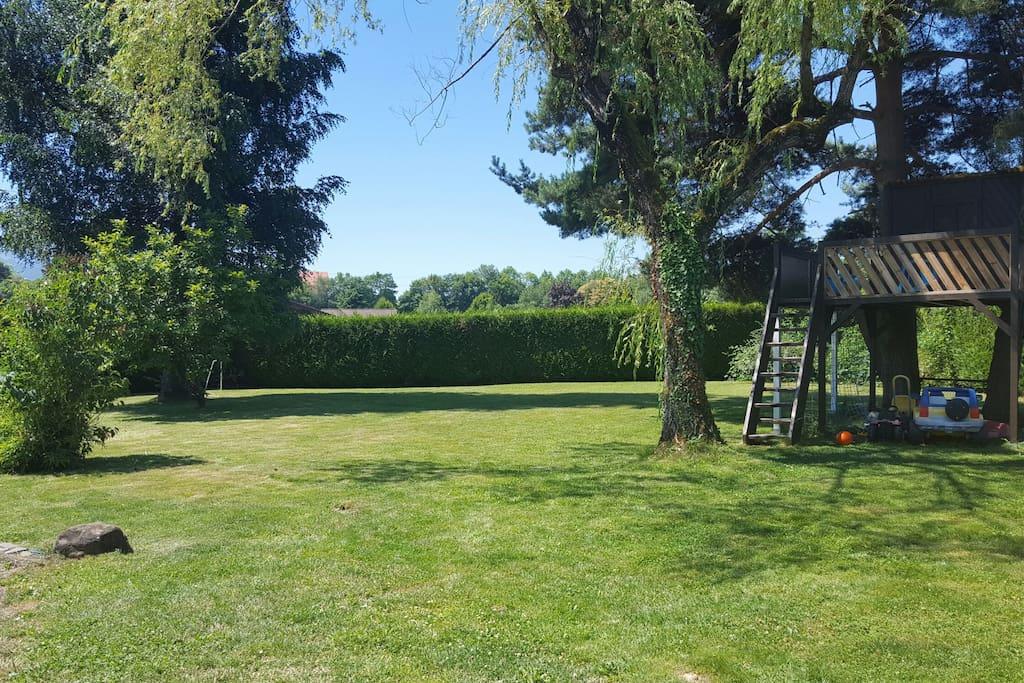 Grand espace vert avec cabane dans les arbres, toboggan et jeux pour enfants