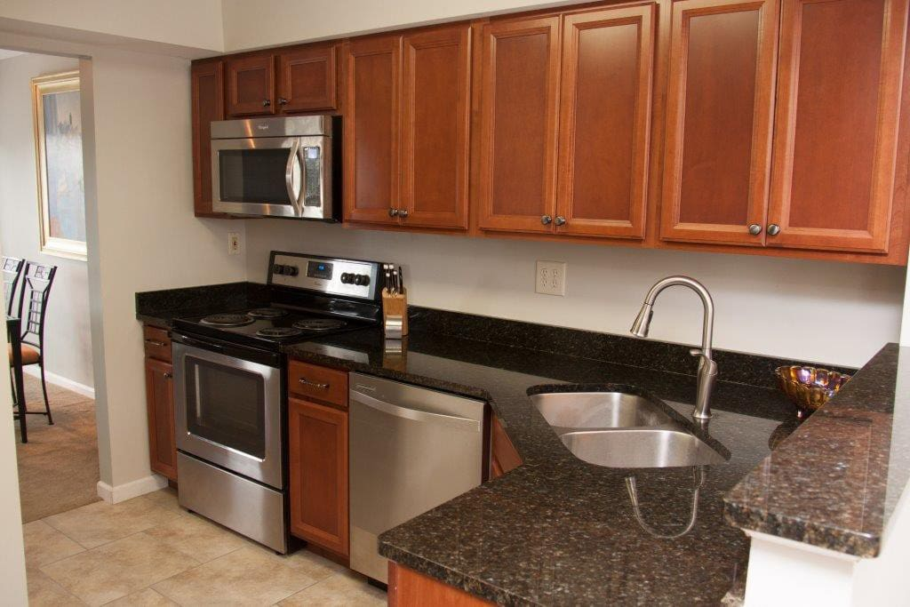 Kitchen offers custom cherry cabinetry, deep stainless steel sink, stainless steel appliances and granite counter tops