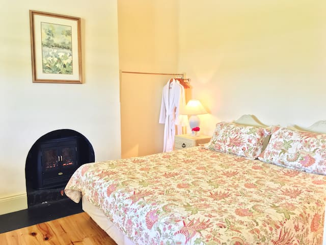 Cottage main bedroom with king size bed, electric wood-look fire and bath robes.