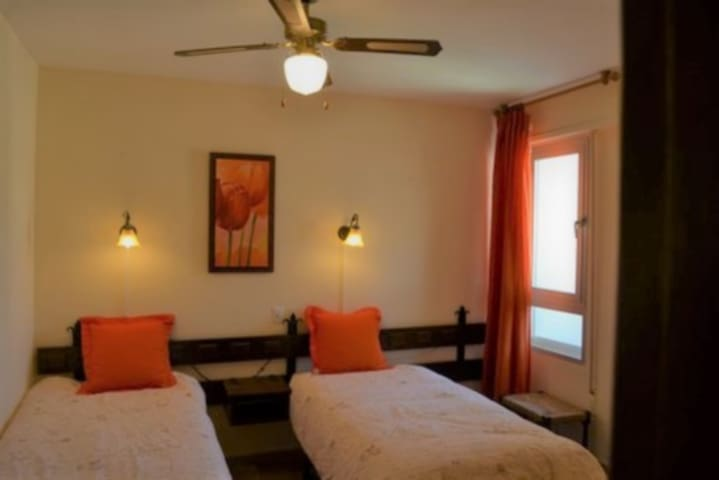 La seconde chambre, comprenant 2 lits d'une personne, idéale pour des enfants ou des invités.