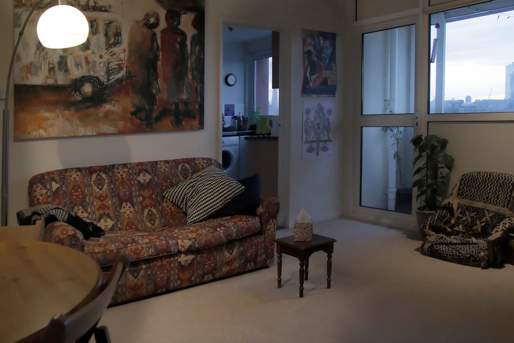 Living room facing sofa-bed, balcony door and kitchen entrance.