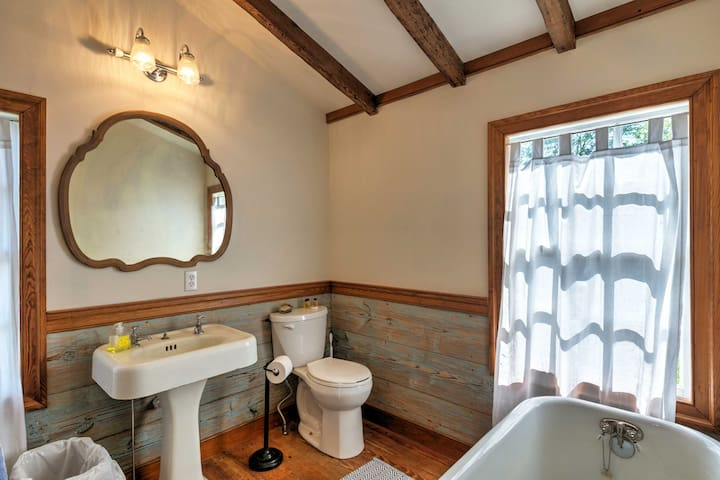 A porcelain sink, vanity mirror, and antique tub adorn this full bathroom.