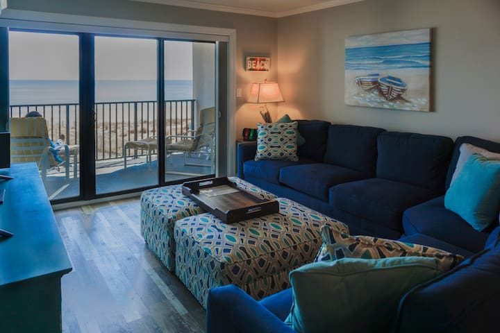 The living room, including new comfortable furniture and oversized footrests with a beautiful view of the ocean.