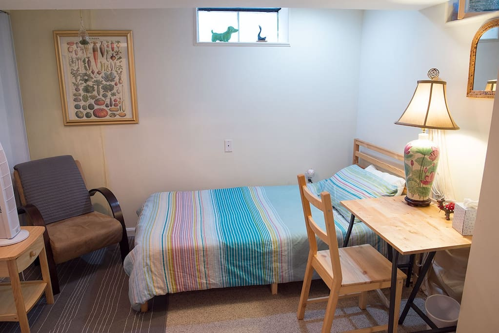 Single bedroom nook w/ desk and nightstand table