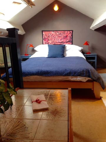 Up on the mezzanine floor is the bedroom with a large velux window with wonderful rooftop views of old Norwich