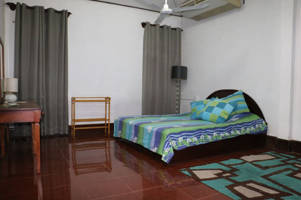 The bedroom - beds in Laos are large. The room has a fan and air conditioning, as well as three windows so you can keep cool.