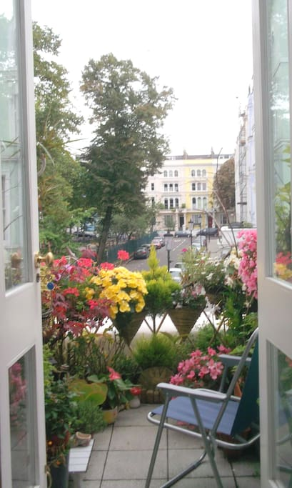 Intimate botanical balcony overlooking a green square and Notting Hill Carnival in August.