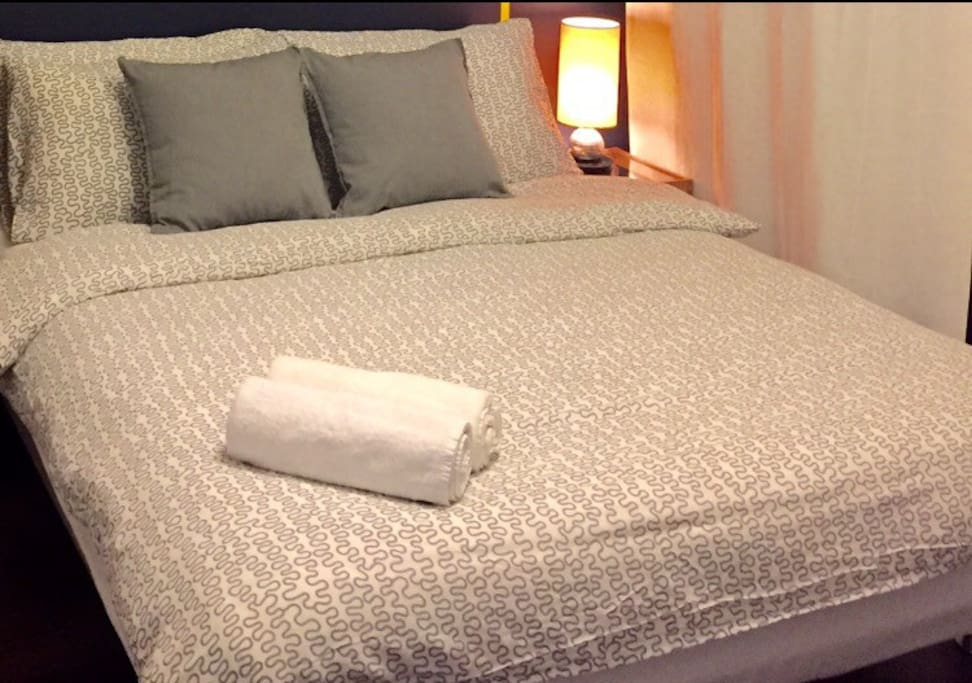Queen bed with bed sets and towels provided.