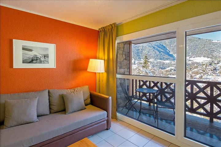 salon avec baie vitrée donnant sur la montagne. Vue des paysages enneigés
