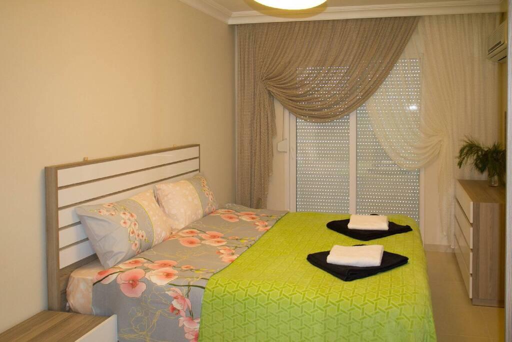 Спальня 1, панорамное окно - оно же выход на балкон, в комнате большой шкаф-купе, комод с зеркалом, две прикроватных тумбочки