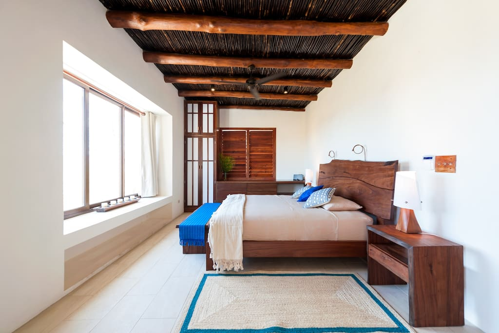 The master bedrooms is bright and airy with stylish decor