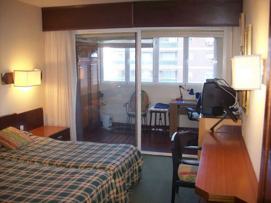 Dormitorio de dos amplias camas con armario empotrado, TV, espacio de estudio.