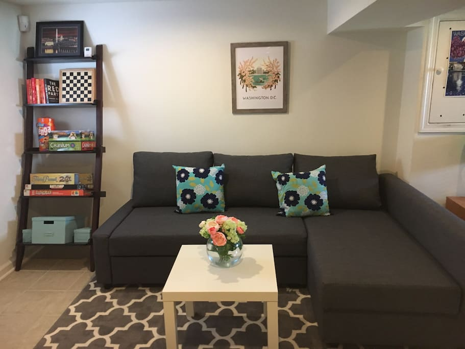 The living room area has a brand new sectional that converts into a comfy full sized bed. There are board games and books on the ladder shelf for guests to enjoy.