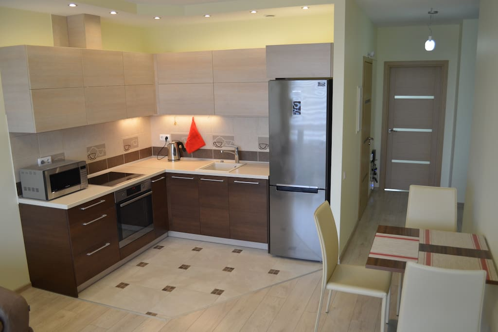 Fully equipped kitchen has everything that you might need - refrigerator, dishwasher, cooker hood, induction hob, oven, microwave, kettle, pots and tools.